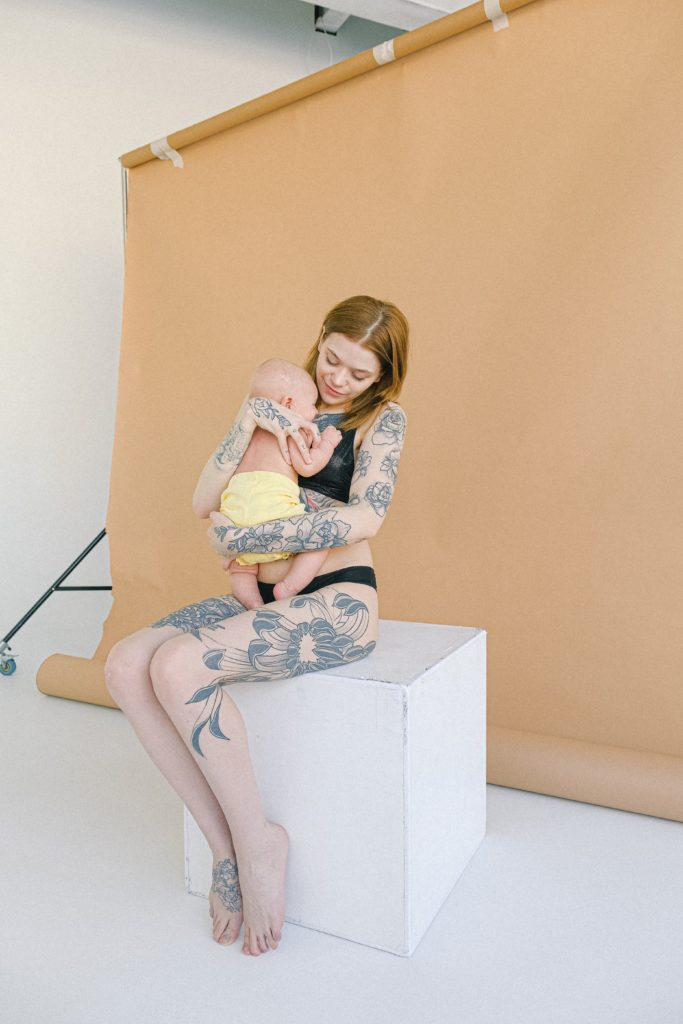 young tattooed mother in underwear embracing newborn baby in jpg 1